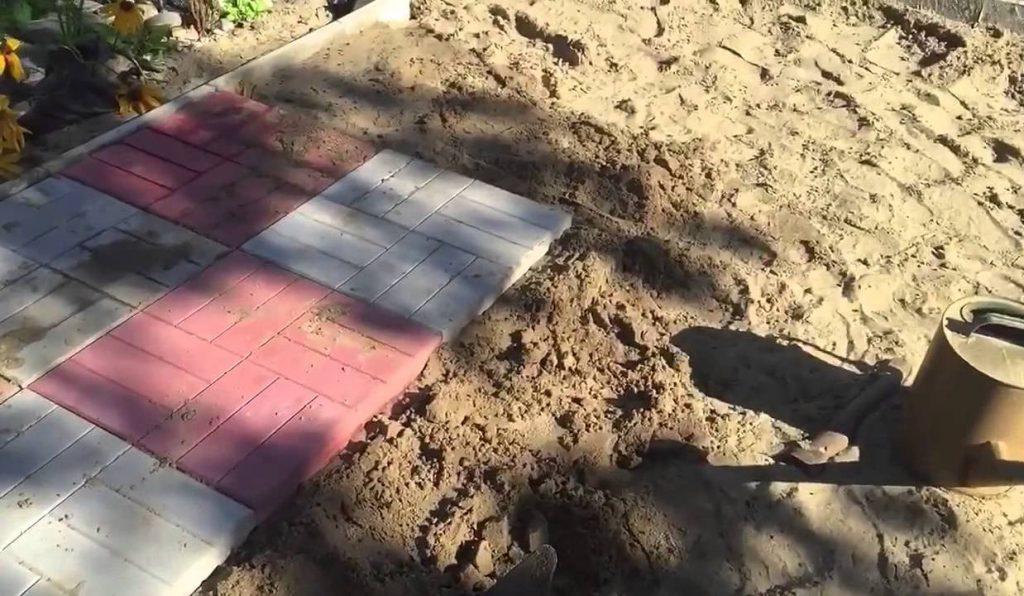 процесс укладки тротуарной плитки под парковку